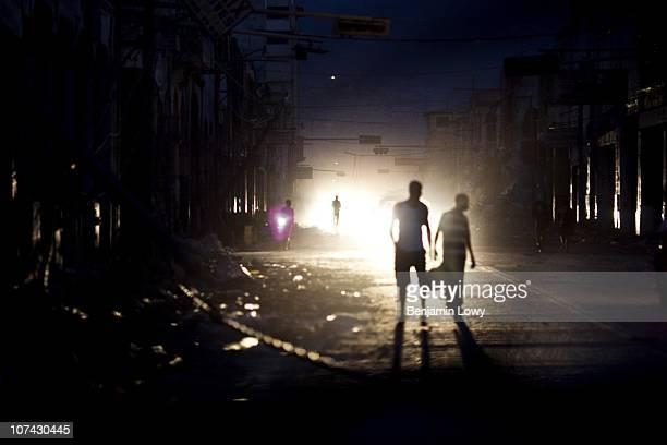 Lit by headlights, Haitians wander through earthquake ravaged downtown Port au Prince on January 31 2010. Haiti was struck by a magnitude 7...
