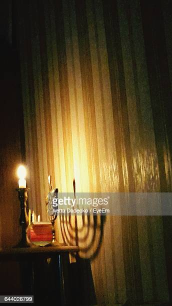 Lit Candle And Menorah And Table By Wall