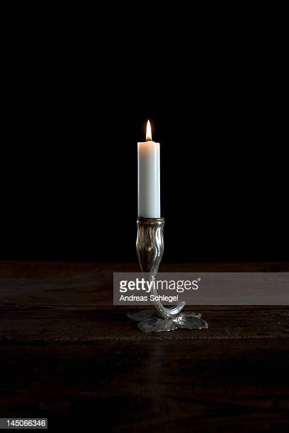 A lit candle in a silver candlestick holder