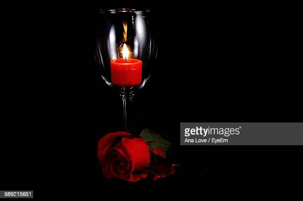 Lit Candle In Wineglass With Rose Against Black Background
