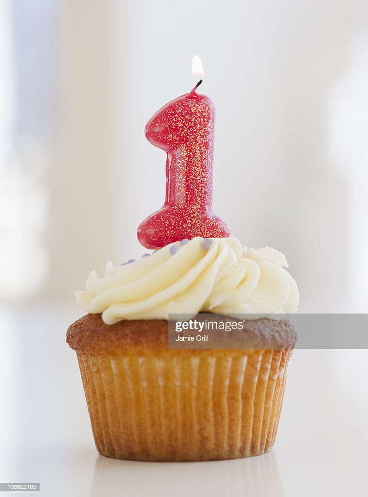 Lit candle on cupcake for first birthday celebration : Stock Photo