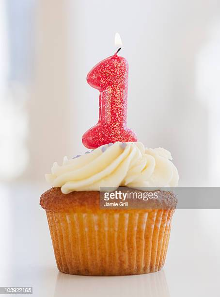 lit candle on cupcake for first birthday celebration - jahrestag stock-fotos und bilder