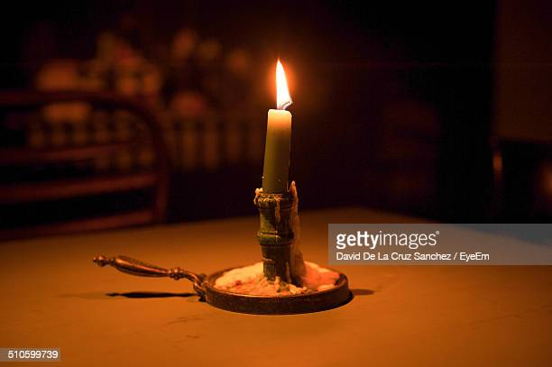 Lit candle on table
