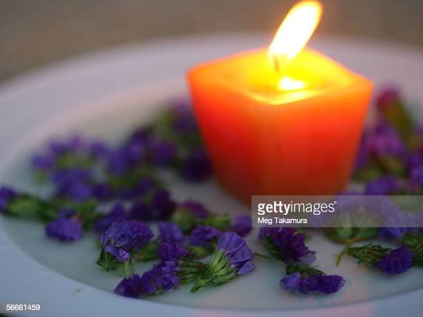Lit candle with a group of flowers in a plate