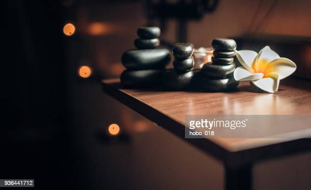 lit candles and black massage stones in zen spa - spa stock pictures, royalty-free photos & images