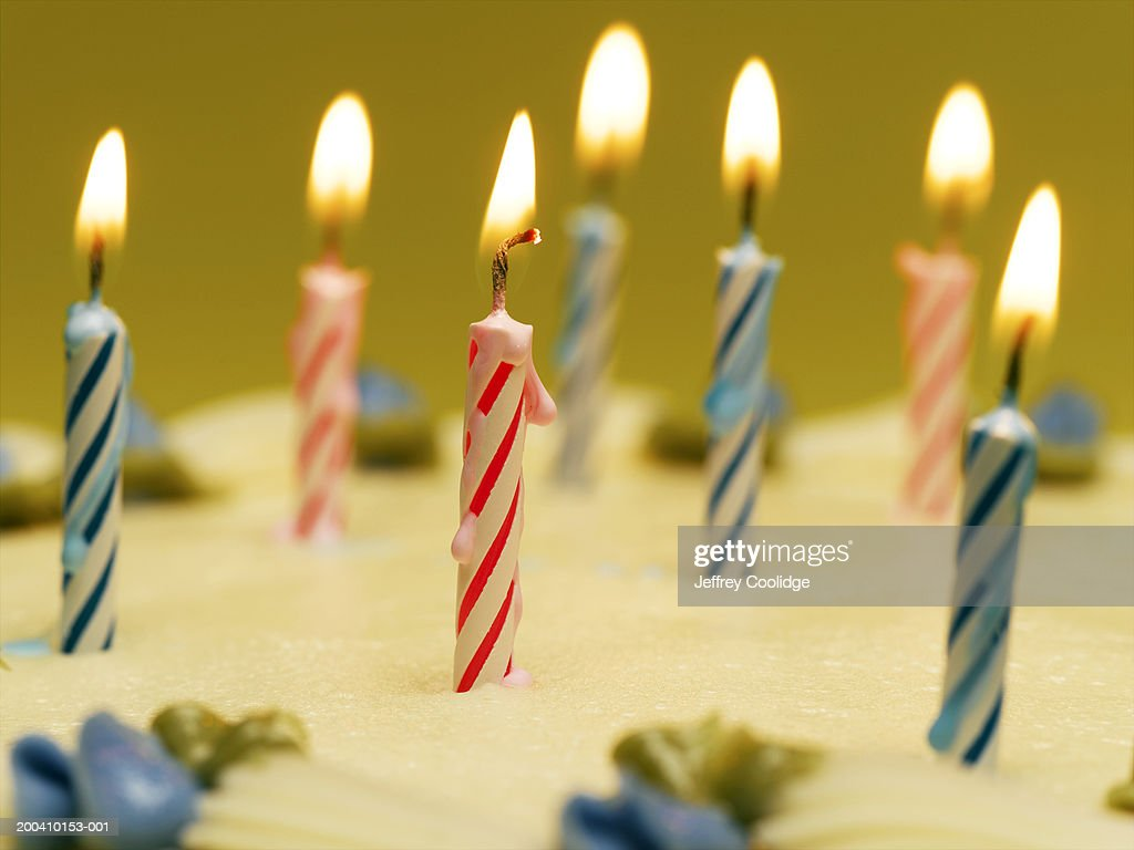 Lit Candles And Blue Decorative Flowers On Birthday Cake Close Up Stock