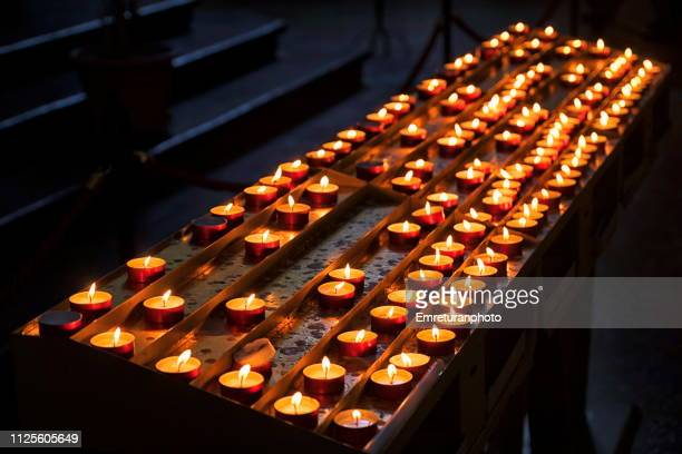lit candles in a church. - emreturanphoto stock pictures, royalty-free photos & images