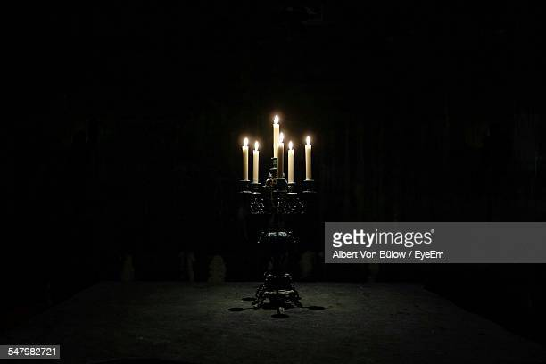 lit candles in darkroom - candlestick holder stock pictures, royalty-free photos & images