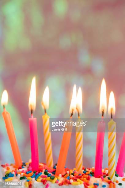 lit candles on birthday cake - birthday candles stock photos and pictures