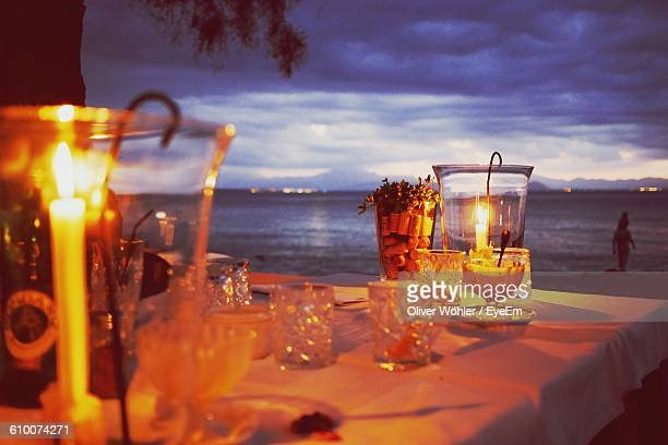 Lit Candles With Glasses On Dinning Table At Beach Restaurant During Dusk