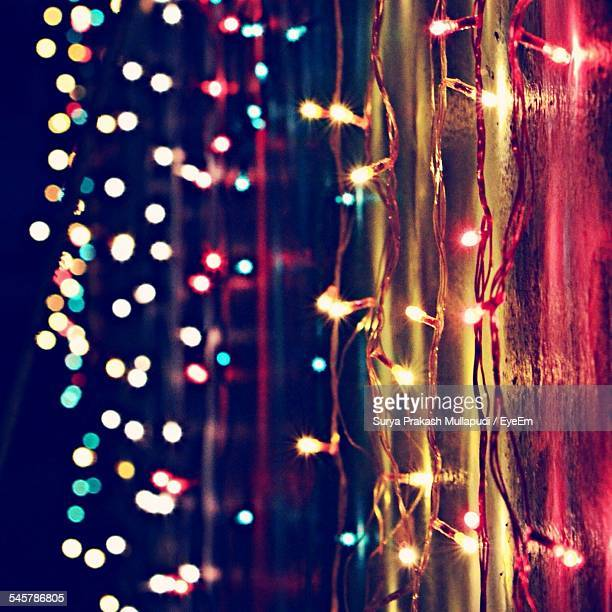 Lit Christmas Lights On Wall Against Defocused Lights