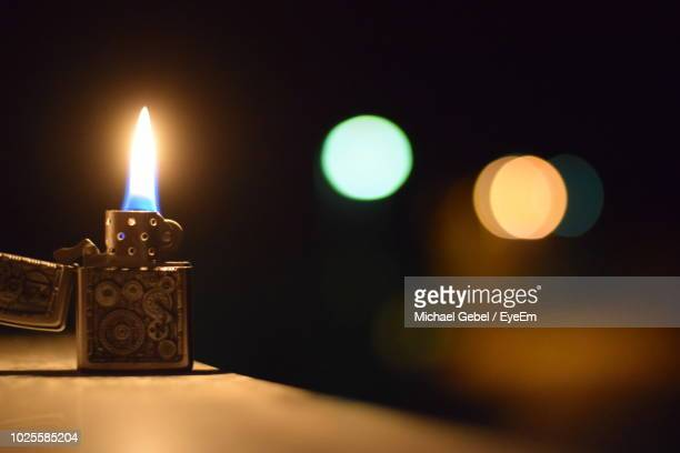 lit cigarette lighter on table at night - cigarette lighter stock pictures, royalty-free photos & images