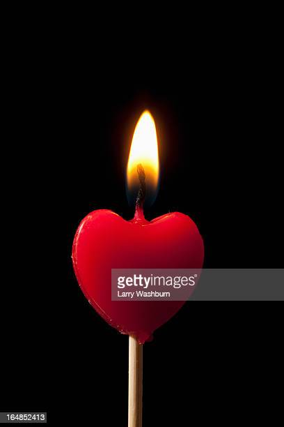 A lit heart shaped candle on a stick