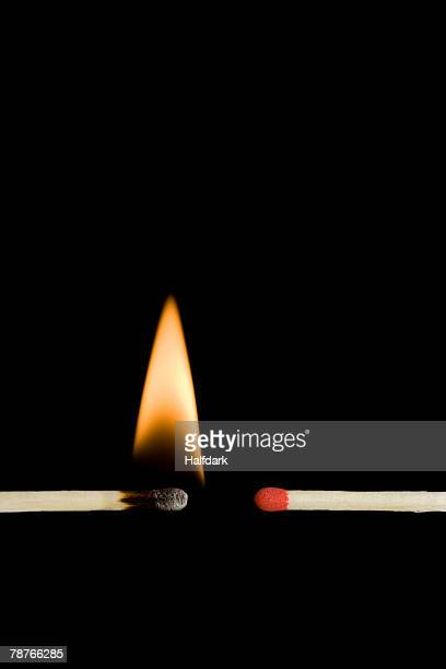 A lit matchstick next to an unlit matchstick