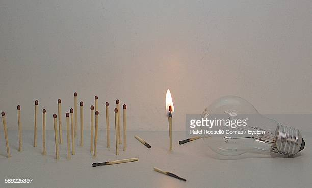 Lit Matchsticks With Light Bulb On Table Against Wall