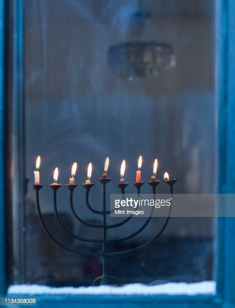 lit menorah on windowsill - menorah stock pictures, royalty-free photos & images