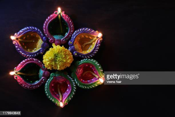 lit painted clay diyas' and marigold flowers/festival of lights/diwali/deepavali - diwali stock pictures, royalty-free photos & images