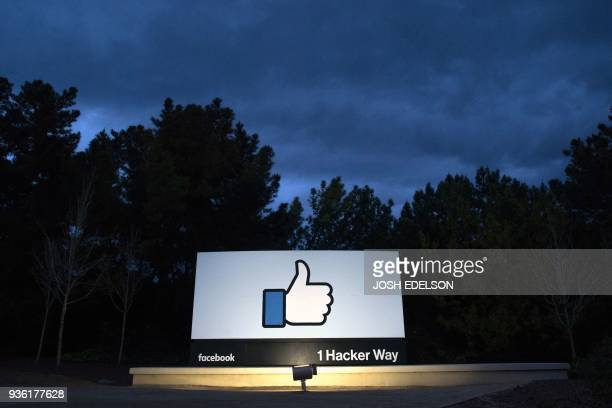 TOPSHOT A lit sign is seen at the entrance to Facebook's corporate headquarters location in Menlo Park California on March 21 2018 Facebook chief...