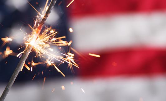 Lit sparkler against a blurred American flag 157582590