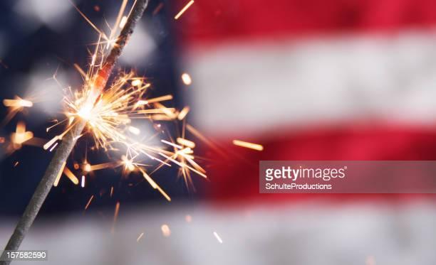 Lit sparkler against a blurred American flag