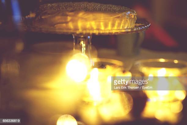 Lit Tea Light Candles By Cake On Table