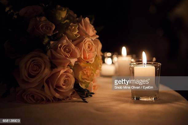 Lit Tea Light Candles By Roses On Table
