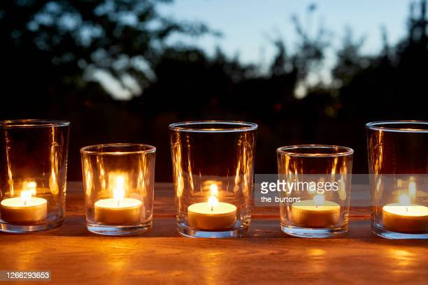 lit tea light candles in glasses in a row on table in garden during sunset - candle stock pictures, royalty-free photos & images