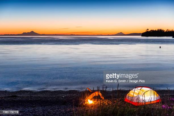 lit tent and campfire on the beach at twilight, hesketh island, homer, southcentral alaska, usa - kachemak bay stock pictures, royalty-free photos & images