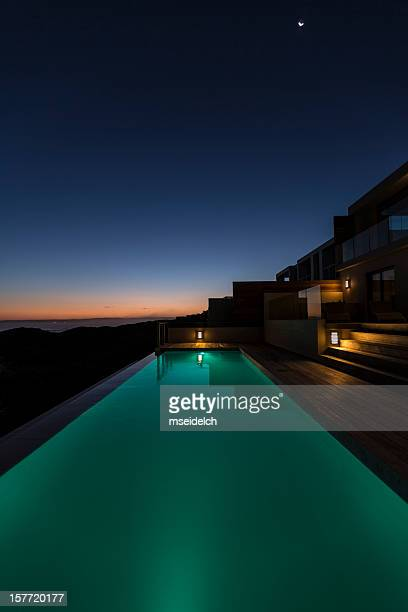 Lit up in ground pool in luxury villa at dusk