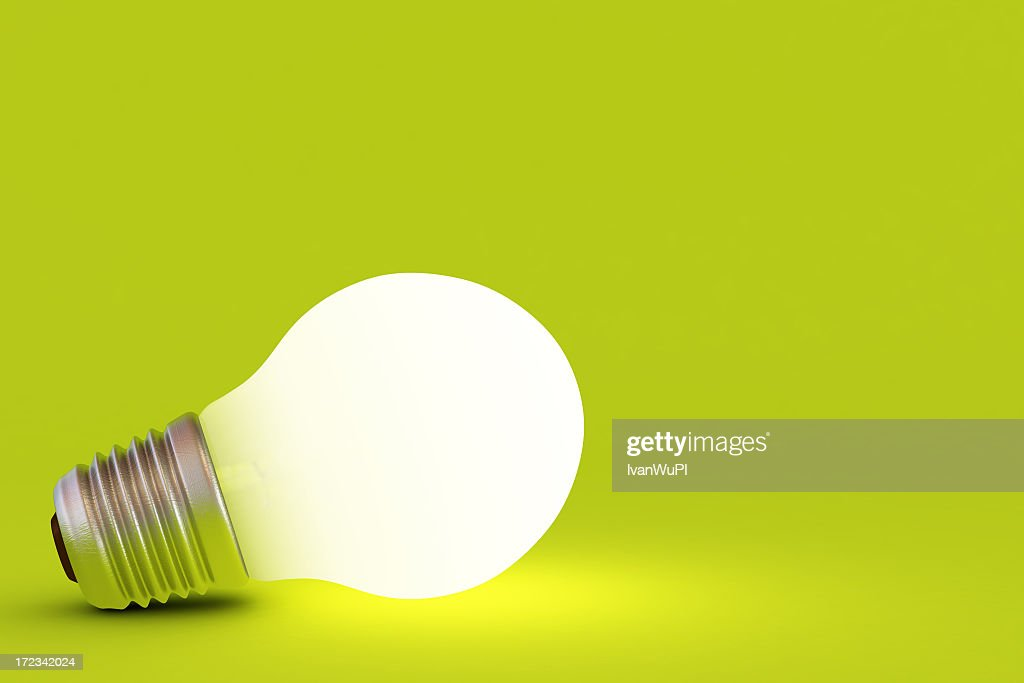A lit up light bulb on a green background : Stock Photo
