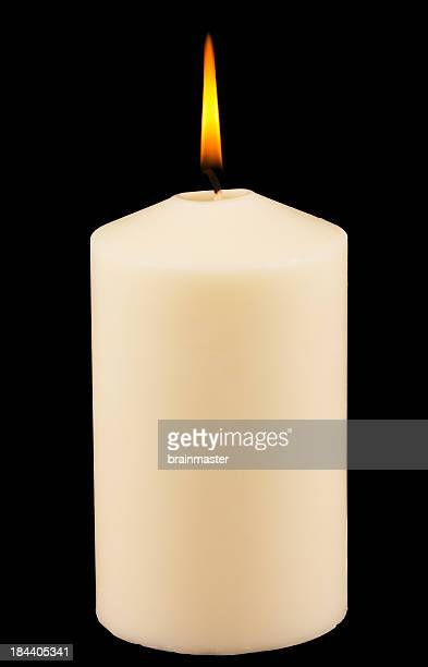Lit white candle against black background