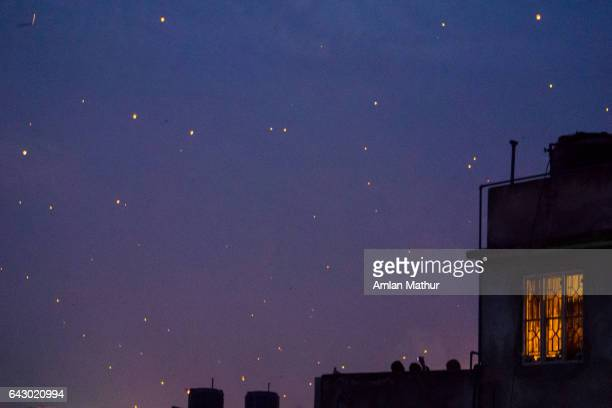lit window against a sky full of lanterns - makar sankranti stock pictures, royalty-free photos & images