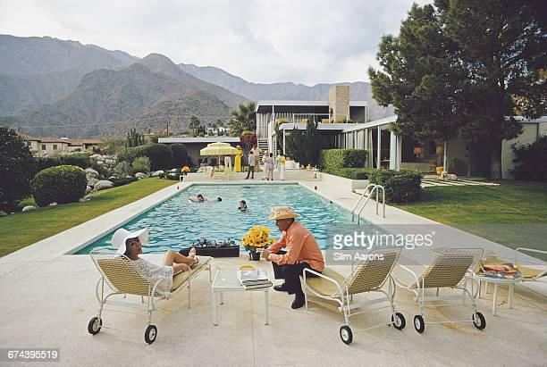 Lita Baron talking with a guest at a poolside party at Nelda Linsk's desert house in Palm Springs California January 1970 The house was designed by...