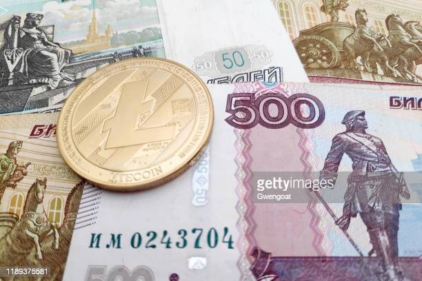 litecoin on top of a stack of russian rubles - gwengoat stock pictures, royalty-free photos & images