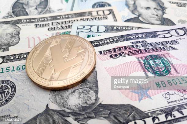 litecoin on top of a stack of us dollars - gwengoat stock pictures, royalty-free photos & images