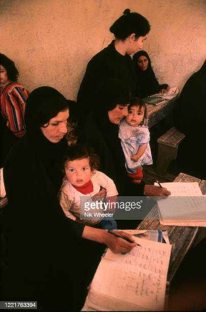 Literacy teacher checks work of chador clad mothers learning reading and writing in classroom near Nasiriyah circa 1978;