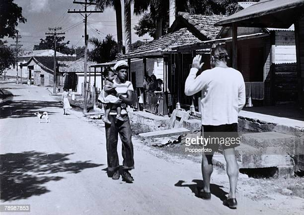 circa 1950 American born writer novelist Ernest Hemingway pictured in the village of Cojimar close to his Cuban farmhouse Finca Vegia as he greets a...