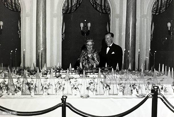 November 1962 English crime writer Agatha Christie cuts the cake watched by Peter Saunders at London's Savoy Hotel to mark the 10th anniversary of...
