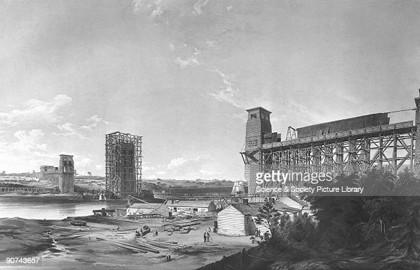 Lithograph by G Hawkins. View taken from the Anglesey Shore showing the piers and scaffolding of the railway bridge. Designed by Robert Stephenson ,...