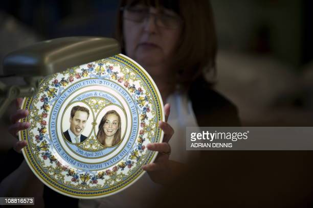 Lithographer Christine Alcock inspects a commemorative royal wedding plate at Caverswall China Company in StokeonTrent central England on February 3...
