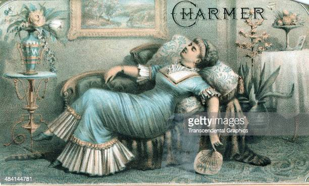A lithographic cigar box label features a woman napping on a fainting couch and is issued in New York City around 1870 She holds a fan and is...