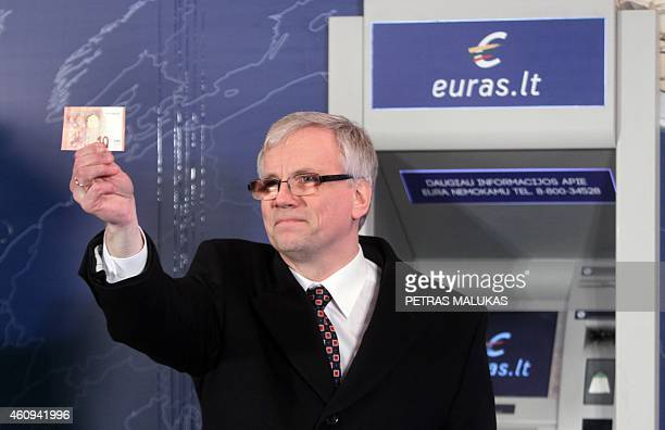 Lithuania Finance Minister Rimantas Sadzus holds euro notes after Prime Minister Algirdas Butkevicius symbolically withdrew a 10 euro note from a...