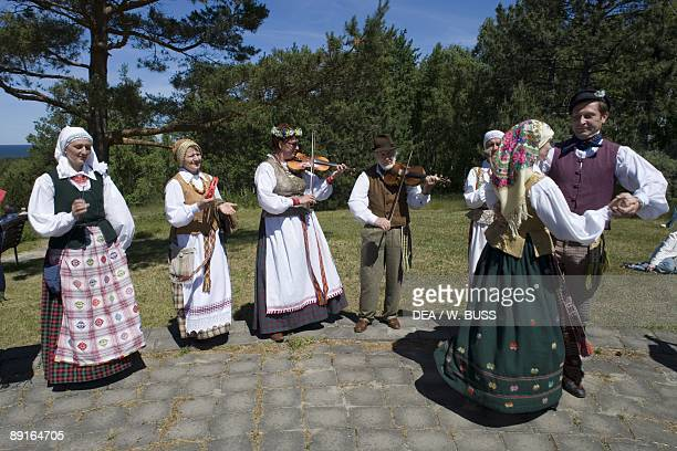 Lithuania Klaipeda County Curonian Spit Nida people wearing traditional costumes playing music and dancing