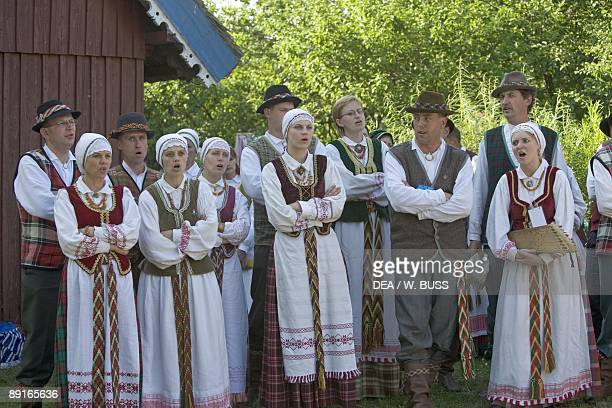 Lithuania Klaipeda County Curonian Spit Nida people wearing traditional costumes singing outside house