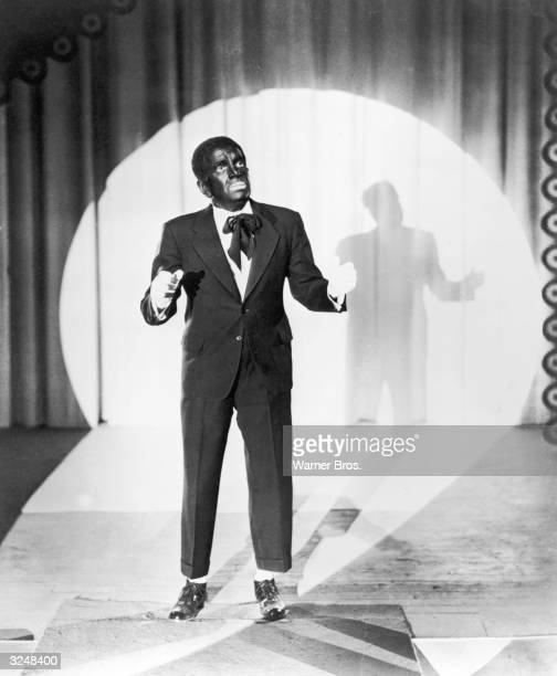 Lithuanian born American actor Al Jolson performs as a minstrel in blackface onstage in a spotlight in a still from the first film to feature sound...