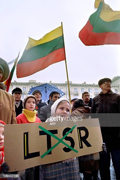 Lithuanian girls stand behind a placard where the letters for 'Soviet and Socialist' are crossed out in Vilnius on March 11 1990 as the newly elected...