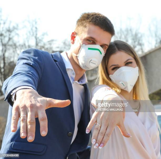 Lithuanian groom Dainius and his bride Ramune pose for the photographer, wearing protective masks against the new coronavirus after their wedding...