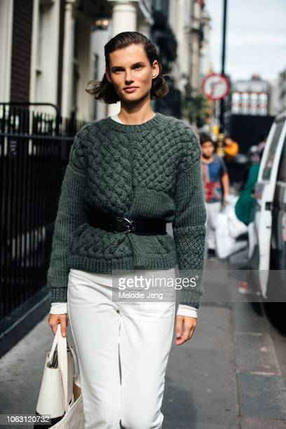 Lithuanian model Giedre Dukauskaite wears a green knit sweater by The Knotty Ones with a black belt and white pants during London Fashion Week...