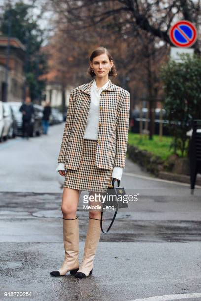 Lithuanian model Giedre Dukauskaite wears a matching checkered suit jacket and skirt a white blouse gray sweater a black Bvlgari bag and gold glitter...