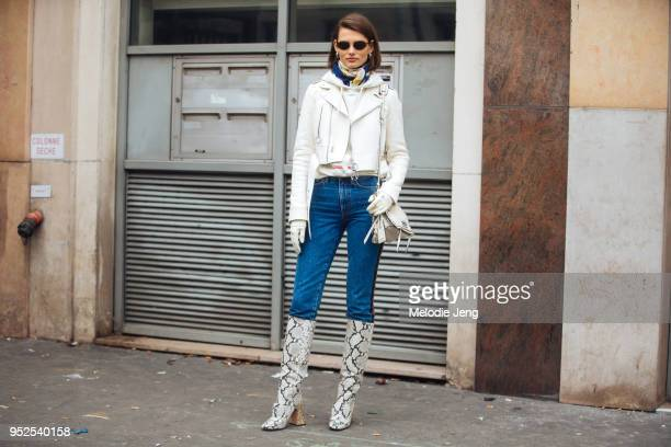 Lithuanian model Giedre Dukauskaite wears frameless sunglasses a cropped white biker leather jacket white gloves a white hoodie a blue scarf a white...
